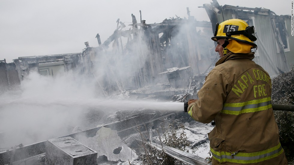 A Napa County firefighter sprays foam on hot spots from a fire at a mobile home park in Napa on August 24.