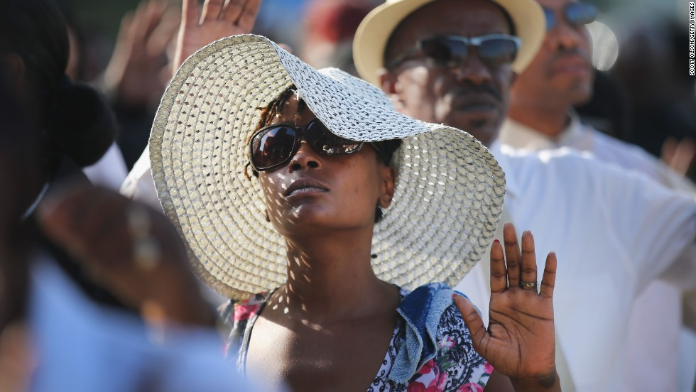 Funeral attendees raise their hands as they wait in line to enter the church on August 25.