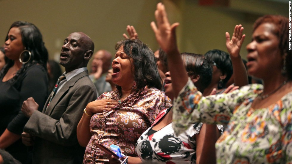 Funeral attendees sing before the start of the service on August 25.