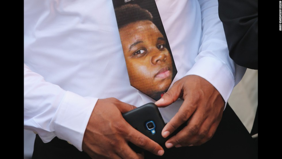 A Brown family member wears a tie with Michael Brown's face on it.