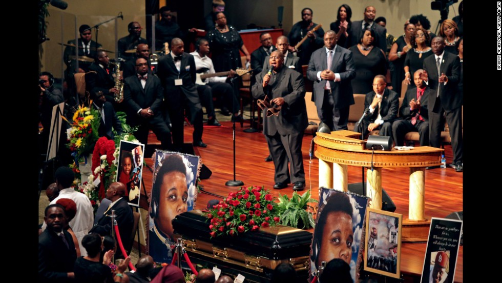 People sing during the funeral for Brown.