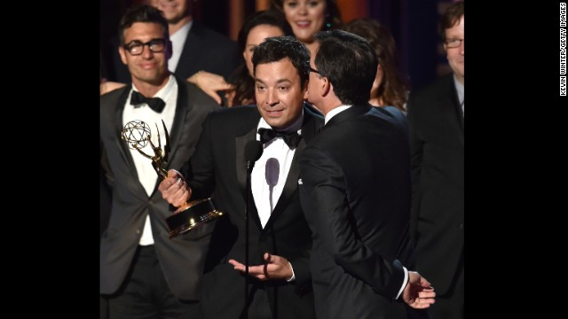 LOS ANGELES, CA - AUGUST 25:  TV personality Stephen Colbert (R) accepts Outstanding Variety Series for 'The Colbert Report' from TV personality Jimmy Fallon (L) onstage at the 66th Annual Primetime Emmy Awards held at Nokia Theatre L.A. Live on August 25, 2014 in Los Angeles, California.  (Photo by Kevin Winter/Getty Images)