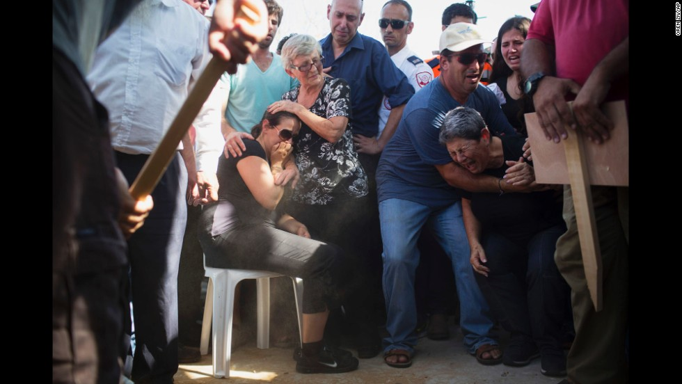 Gila, center, mother of 4-year-old Israeli boy Daniel Tragerman, sits next to his grave during his funeral near the Israel-Gaza border on Sunday, August 24.