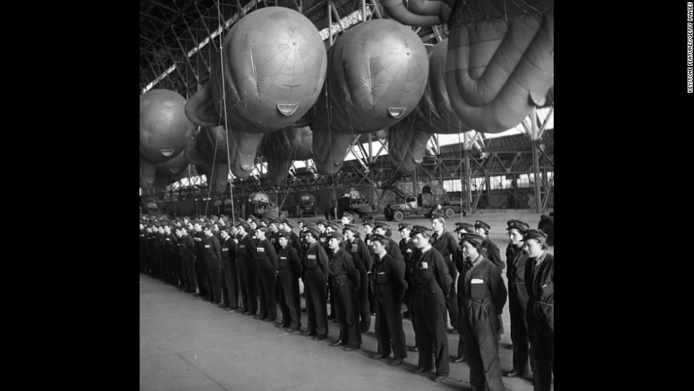 "Balloon operators from Britain's Women's Auxiliary Air Force, or WAAF, report for inspection in a hangar used to store balloons, at a facility in the UK. During World War II, women played a significant role in the war effort. They took jobs in ""defense plants and volunteered for war-related organizations, in addition to managing their households,"" according to the World War II museum in New Orleans."