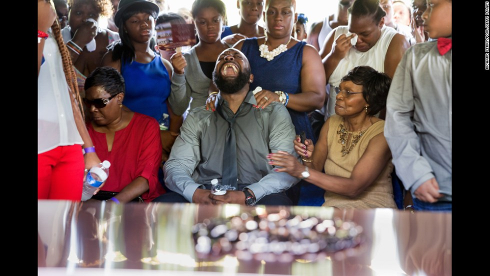 "Michael Brown Sr. yells as his son's casket is lowered into the ground <a href=""http://www.cnn.com/2014/08/25/us/gallery/michael-brown-funeral/index.html"">during his funeral</a> in St. Louis on Monday, August 25. Michael Brown, 18, was shot and killed by police officer Darren Wilson on August 9. His death sparked protests in Ferguson, Missouri, and a national debate about race and police actions."