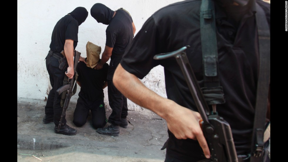Hamas militants grab a Palestinian man suspected of collaborating with Israel before executing him in a central Gaza square on Friday, August 22. Seven suspected informants were shot dead by masked gunmen in front of a crowd outside a mosque, witnesses said. Eleven others were reportedly killed at an abandoned police station.