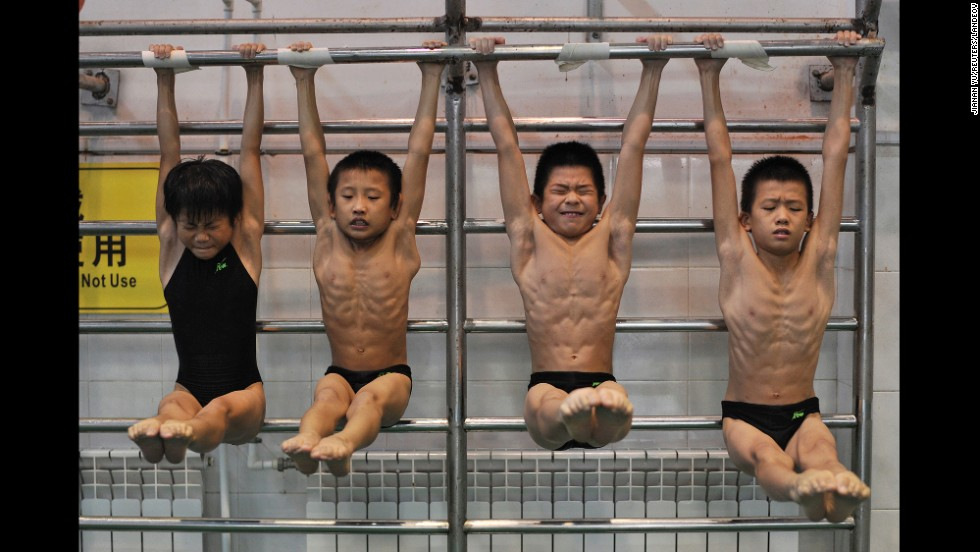 Young divers stretch while training at a sports school in Hefei, China, on Saturday, August 23.