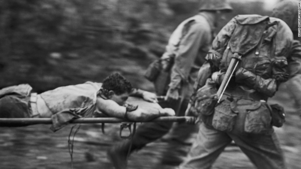Soldiers rush an injured U.S. Marine from a battlefield during the Battle of Okinawa in June 1945. The battle, the bloodiest of the war in the Pacific, raged for nearly three months and heightened U.S. concerns for the enormous casualties that could be anticipated in the planned invasion of Japan's main islands.
