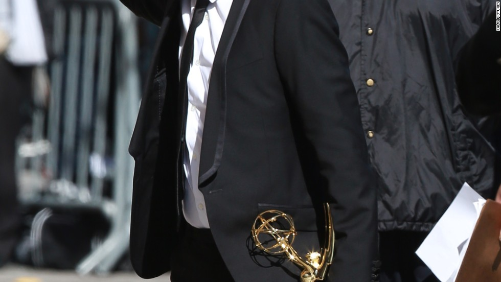 "Aaron Paul waves to fans with one hand while holding his Emmy close with the other as he arrives at ""Jimmy Kimmel Live"" on August 28."