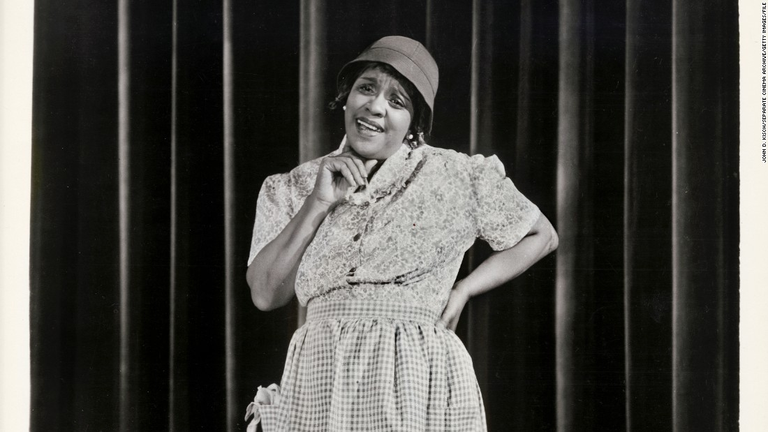 "Considering the early trials Jackie ""Moms"" Mabley had to overcome, her enduring and groundbreaking career in comedy is all the more impressive. After starting off in vaudeville in 1920s New York, she expanded to the silver screen and became the first female comedian to perform at the Apollo Theater. Before Phyllis Diller put on her fright wig and sack dress, Mabley was making audiences double over with her bawdy sense of humor that included frank talk about race. Mabley's talent wasn't widely recognized until the '60s; she died in 1975."