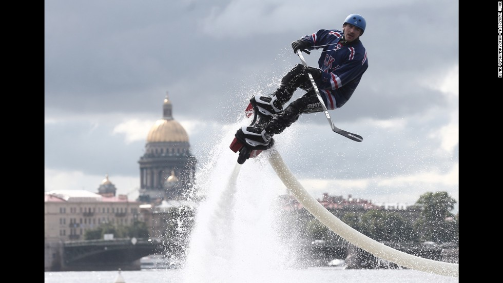 A man in a hockey uniform rides a flyboard Saturday, August 30, as the roster for SKA, a team in the Kontinental Hockey League, is unveiled in St. Petersburg, Russia.