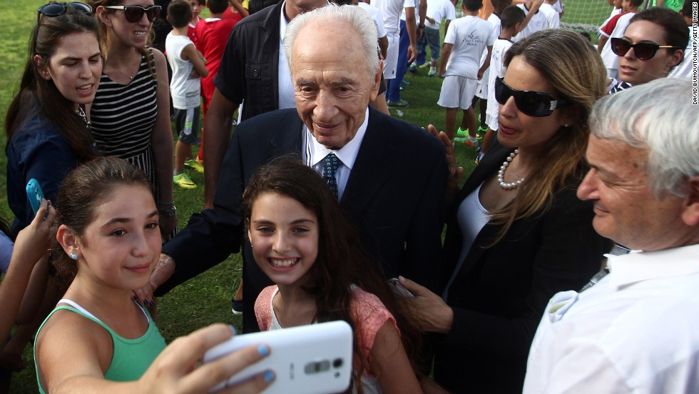 Former Israeli President Shimon Peres poses for a selfie with children on Monday, September 1, during the opening of the Peres Center for Peace in Dorot, Israel. The Center was hosting the Twinned Peace Soccer Schools program that encourages reconciliation between Israeli and Palestinian children from disadvantaged communities.