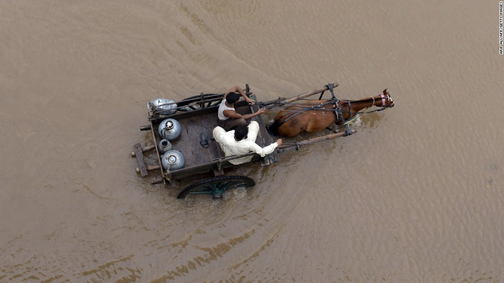 People ride on a horse-drawn cart through floodwaters in Lahore, Pakistan, on September 4.
