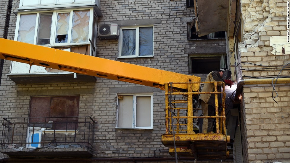 A man repairs damage to a building caused by shelling in Donetsk on September 5.