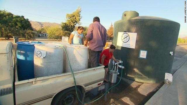 The Gallegos family refills drums with nonpotable water from the county.