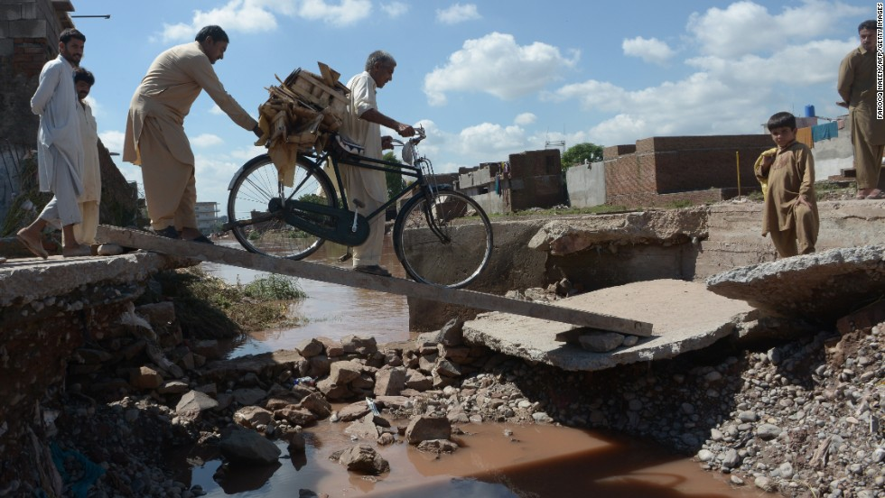 Residents cross a destroyed bridge after flooding in Islamabad, Pakistan, on September 6.