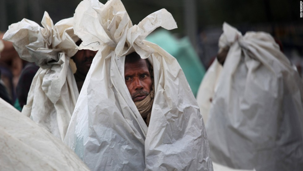 Migrant workers in Srinagar huddle in plastic sheets as they camp on a highway after the area they were living in was inundated by floodwaters on September 6.