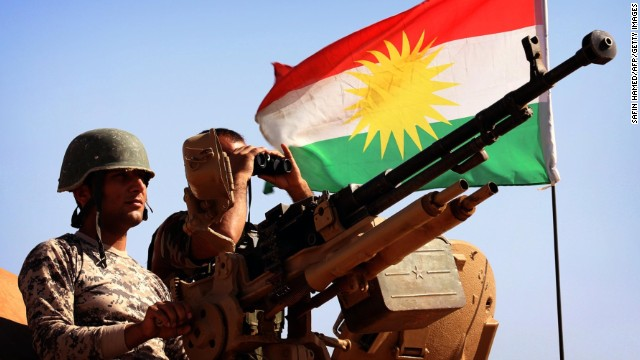 caption:A flag of the autonomous Kurdistan region flies next to Iraqi Kurdish Peshmerga fighters standing on a tank as they hold a position on the front line in Khazer, near the Kurdish checkpoint of Aski kalak, 40 km West of Arbil, the capital of the autonomous Kurdish region of northern Iraq, on September 7, 2014. Kurdish forces in the north have been bolstered by American strikes and recently took control of Mount Zardak, a strategic site east of Mosul that provides a commanding view of the surrounding area, a senior officer said. AFP PHOTO / SAFIN HAMED (Photo credit should read SAFIN