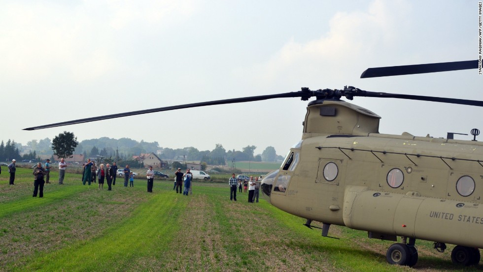Villagers look at the U.S. helicopters and their crews. Six other U.S. helicopters also made unplanned landings in the nearby village of Nowa Wies because of the weather.