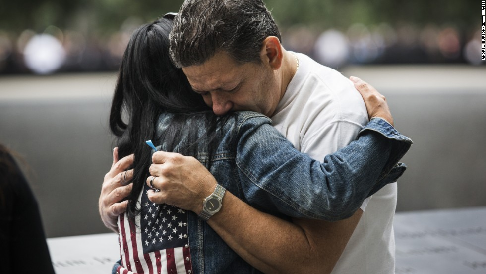 Eileen Esquilin hugs her husband, Joe Irizarry, while mourning the loss of her brother, Ruben Esquilin Jr., during memorial observances in New York.