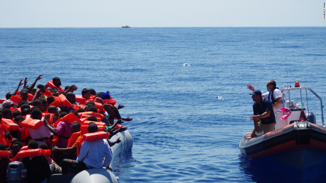 "A lifeboat from rescue ship ""Phoenix"" approaches refugees, offering drinking water. ""We never approach a boat with our boat because it's rather big, so we approach cautiously with a dingy. The first thing we do is start giving out life jackets,"" said MOAS director Martin Xuereb."