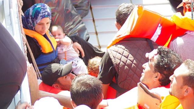 "Refugees receive help from rescue boat ""Phoenix."""