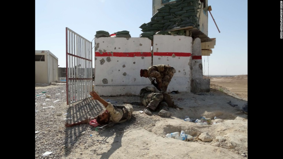 A member of Iraq's security forces helps comrades who were wounded in an attack at a military post Sunday, September 7, in Iraq's Anbar province. The governor of Anbar province, Ahmed al-Dulaimi, was also hurt in the attack.