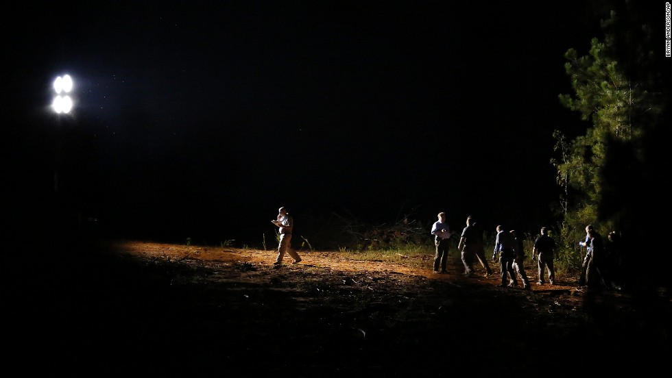 "A group of investigators gather under a light at a crime scene Tuesday, September 9, in Camden, Alabama. Timothy Jones Jr., 32, faces five murder counts in South Carolina after his five children, ages 1 to 8, <a href=""http://www.cnn.com/2014/09/11/justice/five-children-found-dead/index.html"">were found dead in Alabama.</a>"