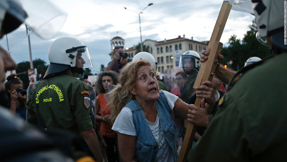 A protester in Thessaloniki, Greece, argues with a police officer during a rally against austerity measures Saturday, September 6. That same day, Greek Prime Minister Antonis Samaras announced cuts to unpopular taxes that were introduced at the height of the country's debt crisis.