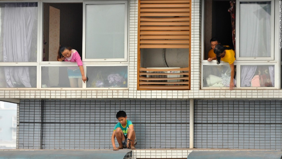 "A 12-year-old boy sits outside a window of his 11th-floor apartment as his relatives try to ask him to come back inside in Yibin, China, on Monday, September 8. The boy was afraid of being punished by his mother for not finishing his homework, according to the <a href=""http://www.globaltimes.cn/content/880633.shtml"" target=""_blank"">Global Times.</a> After a two-hour standoff, police and family members persuaded him to come inside."