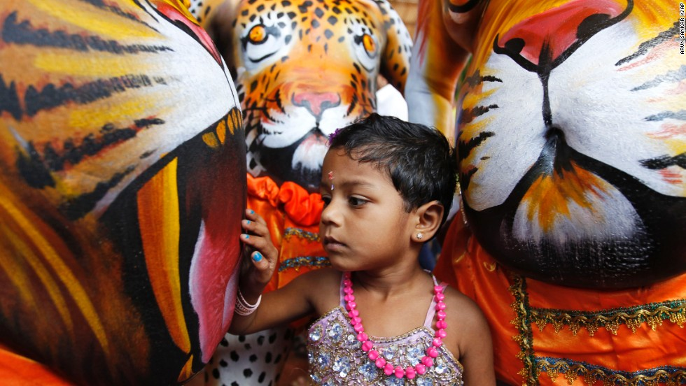 "A child touches the belly of an artist whose body is painted in the likeness of a tiger to perform the annual ""Pulikali,"" or Tiger Dance, in Thrissur, India, on Wednesday, September 10. The colorful folk art revolves around the theme of tiger hunting and is performed to entertain people during Onam, an annual harvest festival."