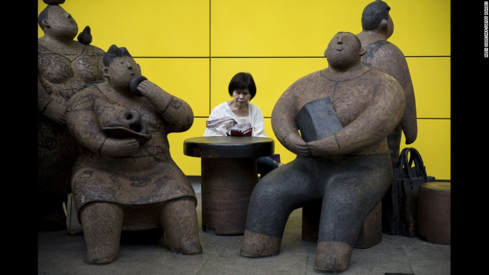 A woman reads on her cell phone next to sculptures by artist Rosanna Li Wei-han outside a railway station in Hong Kong on Saturday, September 6.
