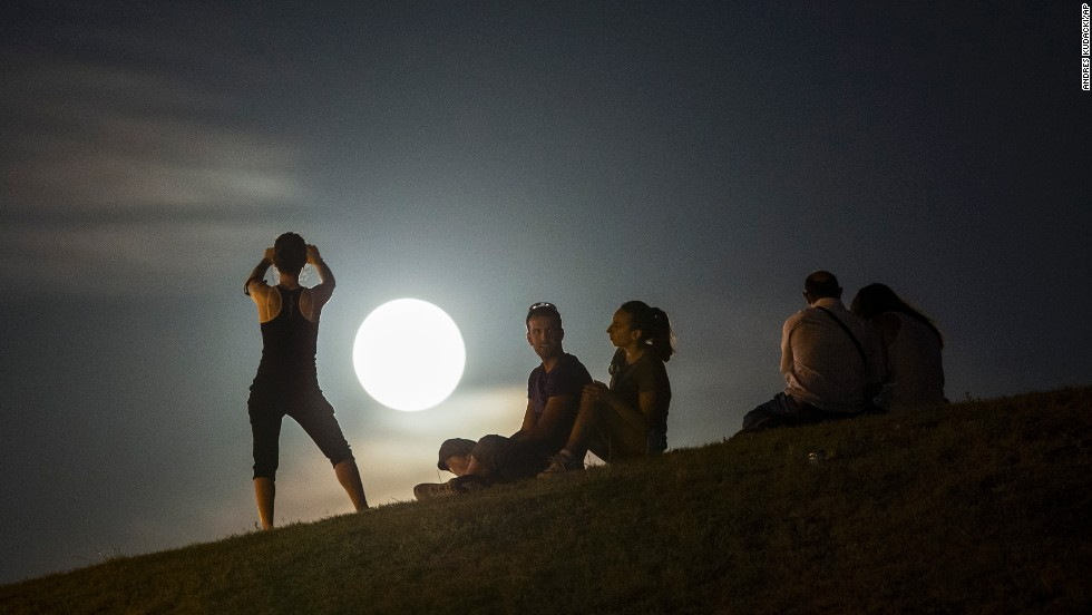 "People in Madrid watch a perigee moon, also known as a ""supermoon,"" as it rises in the sky Tuesday, September 9. The phenomenon occurs when the moon becomes full on the same day as its perigee -- the point in the moon's orbit when it is closest to Earth. <a href=""http://www.cnn.com/2014/09/05/world/gallery/week-in-photos-0905/index.html"">See last week in 30 photos</a>"
