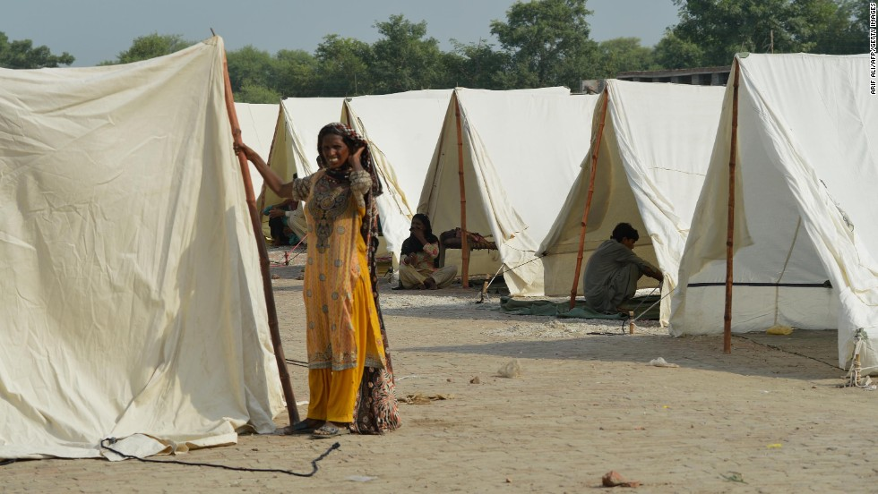 A woman displaced by recent flooding stands amid relief tents at the Athara Hazari area in Jhang, Pakistan, on September 11.