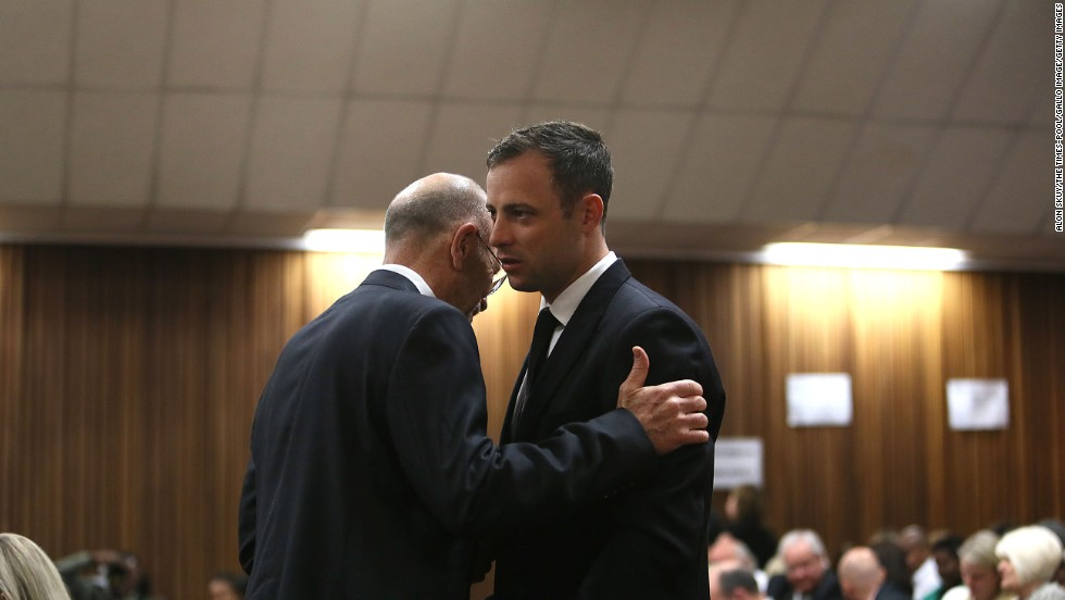 Pistorius speaks with his uncle Arnold Pistorius during his trial at the Pretoria High Court on Friday, September 12.