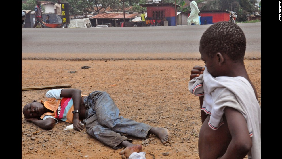 A child stops on a Monrovia street September 12, 2014, to look at a man who is suspected of suffering from Ebola.