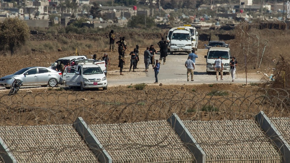 "Al-Qaeda-linked rebels from Syria gather around vehicles carrying U.N. peacekeepers from Fiji before releasing them Thursday, September 11, in the Golan Heights. The 45 <a href=""http://www.cnn.com/2014/09/01/world/meast/syria-crisis/index.html"" target=""_blank"">peacekeepers were captured </a>in the Golan Heights after rebels seized control of a border crossing between Syria and the Israeli-occupied territory."