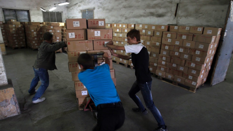 Workers unload supplies from Russia in Luhansk, Ukraine, on September 13. More than 200 Russian trucks entered Ukraine with supplies for the city, which has been cut off from electricity and water for weeks.