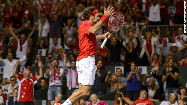 Roger Federer jumps for joy after completing his singles victory over Fabio Fognini in the Davis Cup semifinal.