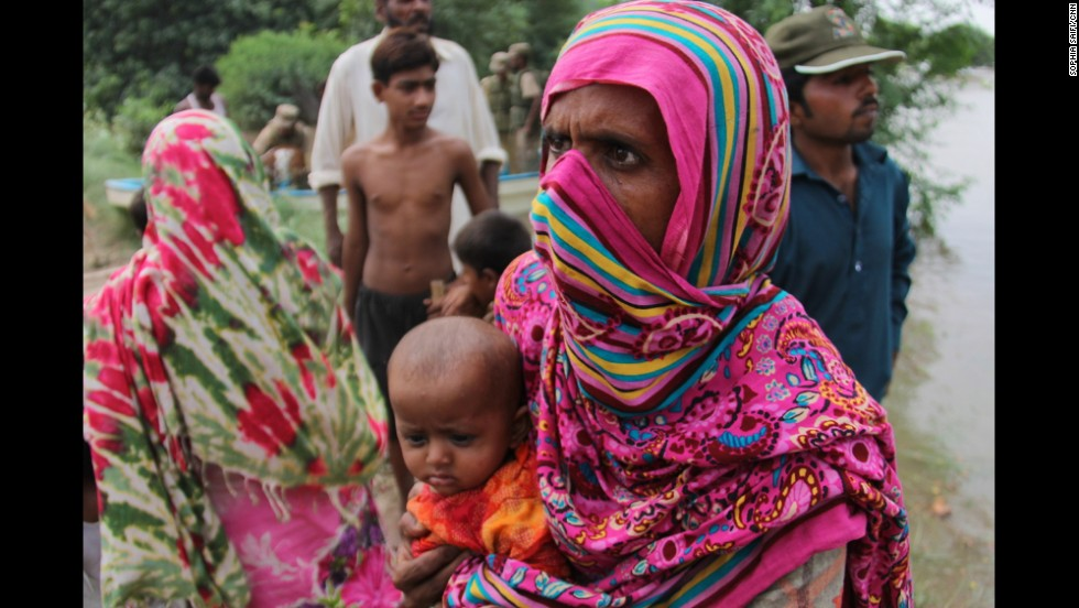 A woman and her child get off a military rescue boat after leaving their village near Multan on September 13.
