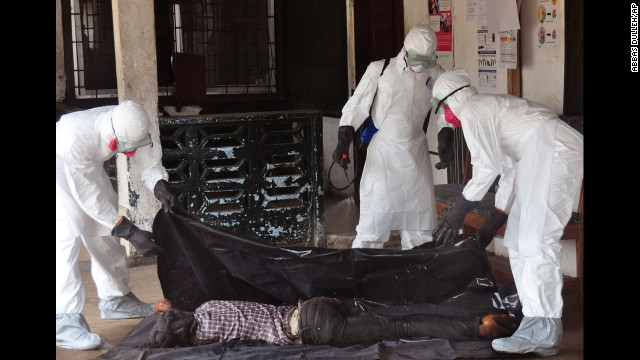 Health workers in protective gear move the  body of a person that they suspect dyed form the Ebola virus in Monrovia, Liberia, Tuesday, Sept. 16, 2014. The number of Ebola cases in West Africa could start doubling every three weeks and it could end up costing nearly $1 billion to contain the crisis, the World Health Organization warned Tuesday.  (AP Photo/)