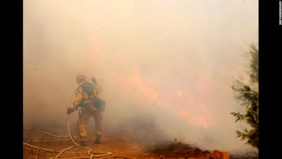 A firefighter is shrouded in smoke near Fresh Pond on September 17.
