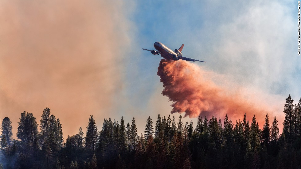 An airplane drops fire retardant over a fire at Bass Lake on September 14.