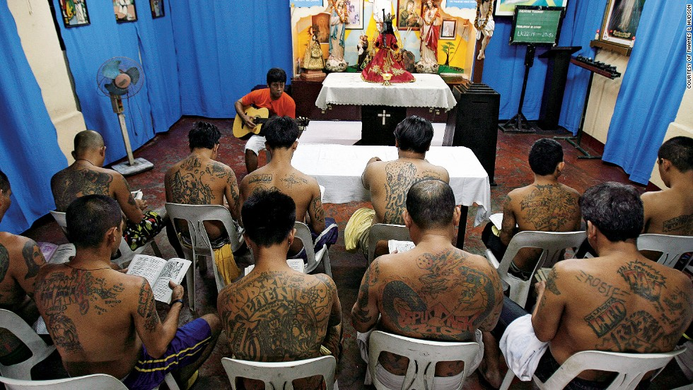 Inmates of the Makati City jail in Manila attend Catholic worship in 2010. Their tattoos identify them as members of particular gangs.