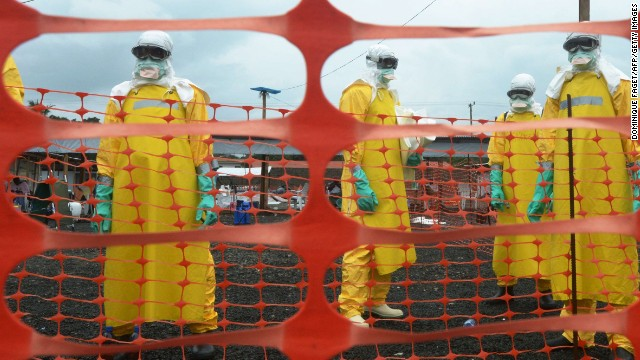 Workers wearing personal protective equipment stand inside the contaminated area at the ELWA Hospital in Monrovia, Liberia. The hospital is run by Médecins Sans Frontières, also known as Doctors without Borders.