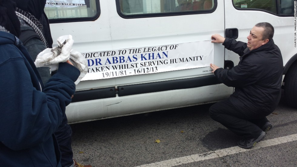 Henning attaches a sticker to the side of the ambulance he was driving. He dedicated his ambulance to the memory of Dr. Abbas Khan, a British doctor apparently arrested and allegedly later murdered by the Syrian regime as he carried out aid work in Syria.