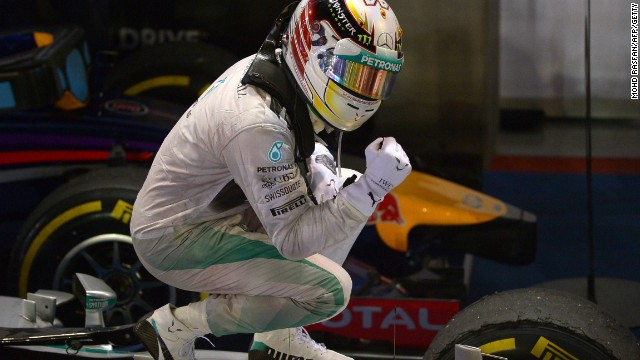 Lewis Hamilton poses on top of his car after winning the Singapore GP to take the title lead.