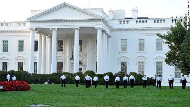 Uniformed Secret Service officers walk along the lawn on the North side of the White House in Washington, Saturday, Sept. 20, 2014. The Secret Service is coming under intense scrutiny after a man who hopped the White House fence made it all the way through the front door before being apprehended.