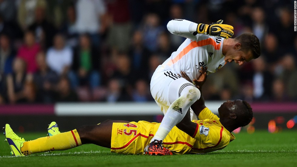 West Ham goalkeeper Adrian, top, and Liverpool forward Mario Balotelli clash after a Balotelli tackle Saturday, September 20, in London. West Ham won the Premier League match 3-1.