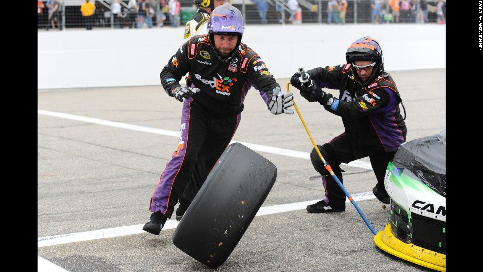 Two members of Denny Hamlin's pit crew change a tire during the NASCAR Sprint Cup race in Loudon, New Hampshire, on Sunday, September 21.